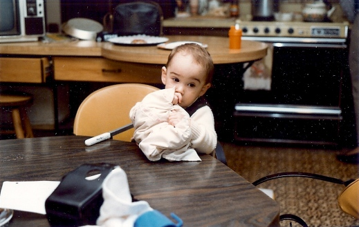 This is me on a visit to Grandma and Pop-Pop's. My sippy cup is the orange one on the counter behind me. My brother's is the blue cup in the foreground. Both once held coffee.